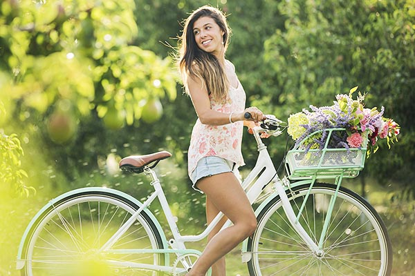 Девушка на велосипеде с корзинкой цветов на руле - ретро стиль.