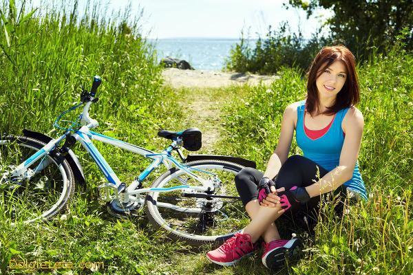 Девушка отдыхает на природе от поездки на велосипеде.