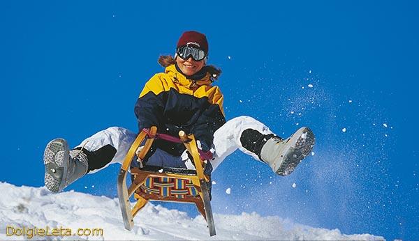Радостная девушка управляет санками, маневрируя скатывается со снежной горы.