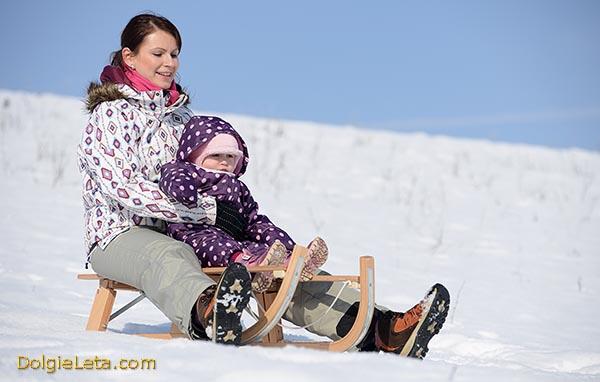 Мама с маленьким малышом катается на зимних санках с горки.
