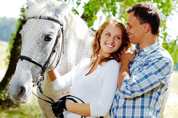 На фото молодая семейная пара с белой лошадью.