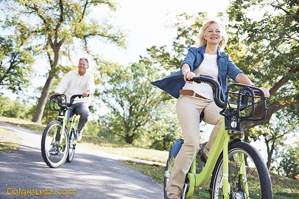 Счастливые мужчина и женщина в возрасте на велопрогулке катаются на велосипедах.