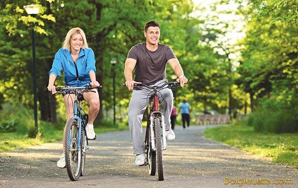 Польза езды на велосипеде - молодая пара на велопрогулке.