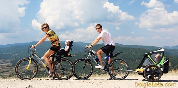Родители на велопрогулке катают детишек  на велосипедных креслах.