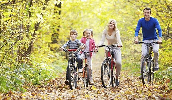 Родители с детишками катаются на велосипедах осенью. - Чем полезна езда на велосипеде.