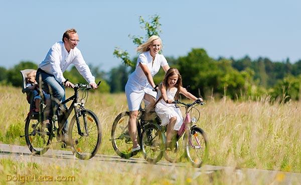 Семейные велопоездки родителей с маленькими детишками на велосипедах.