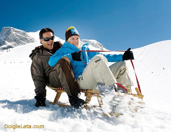 Счастливая семейная пара катается на зимних санках с гор. - Отзывы об использовании саней.