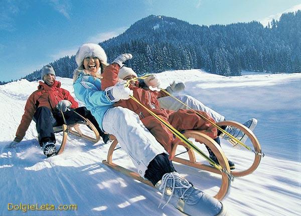 Счастливая и радостная семья с ребенком катается на деревянных санках с гор.