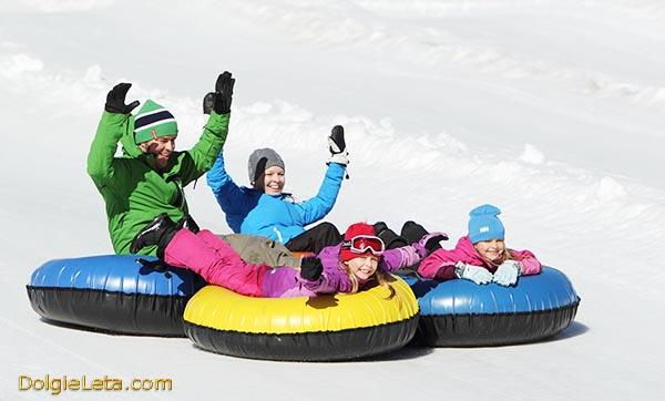 Счастливые родители с детьми катаются на зимних надувных санках ватрушках тюбингах с горок. Выбор зимних санок.