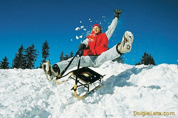 Счастливая девушка съезжает со снежной горы на санках.