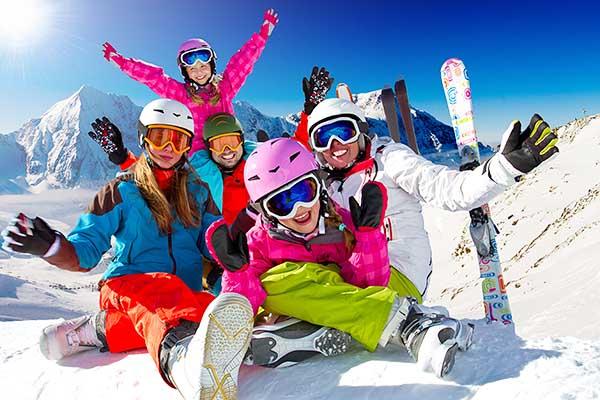 Счастливая семья на зимних новогодних каникулах катается на горных лыжах вместе с детьми.