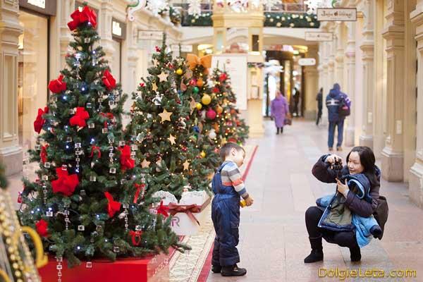 Мама фотографирует ребенка в магазине ГУМ в Москве - праздничные новогодние зимние каникулы.