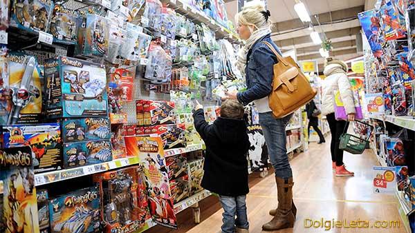 Малыш с мамой выбирает игрушку в магазине.