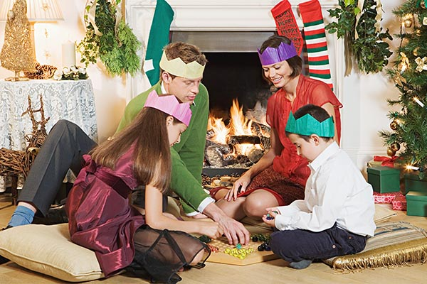 Родители с детьми играют в настольные игры на зимних каникулах.