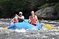 Рафтинг - активный семейный отдых - родители с детьми на резиновой лодке сплавляются по быстрой реке.