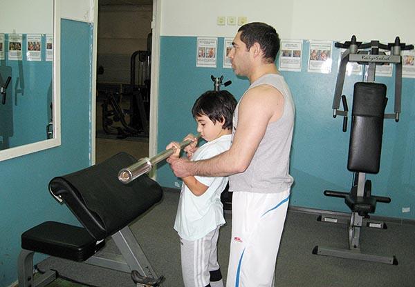 Ребенок с папой занимается в тренажерном зале.