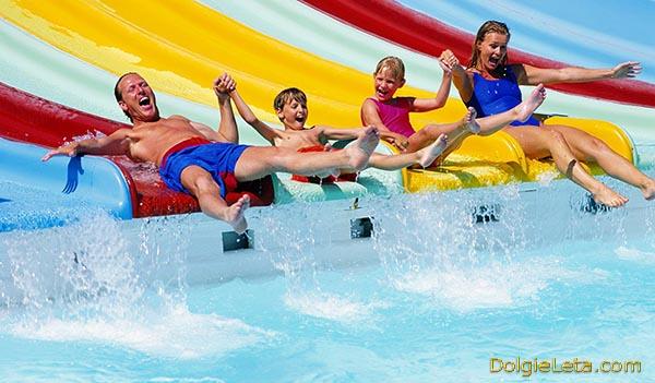 Родители с детьми катаются с горок в закрытом аквапарке - семейный отдых на зимних каникулах.