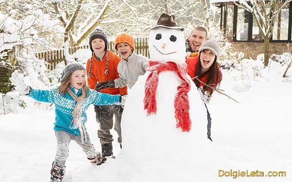 Счастливая семья с детишками лепят снеговика на зимних каникулах.