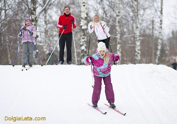 Семья катается на лыжах с горки